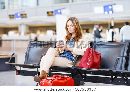 Young woman at international airport sitting waiting for canceled or delayed flight. Female passenger at terminal, indoors.  Travel, business, people concept. - stock photo