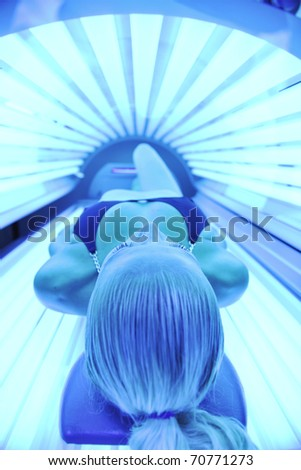 young woman at laying on solarium bed and get brown skin tone ready for summer - stock photo