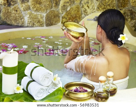 Young woman at spa centre taking milk bath - stock photo