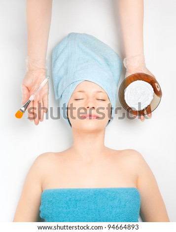 Young woman at spa procedures applying mask - stock photo