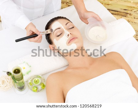 Young woman at spa salon with cosmetic mask on face. High angle photo - stock photo