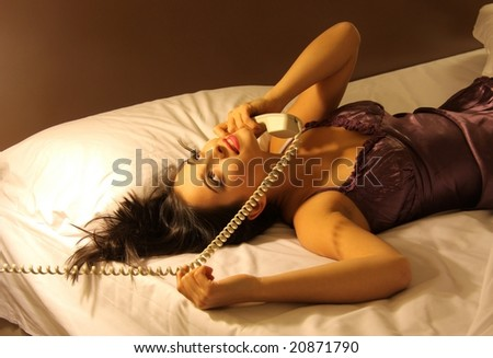young woman at telephone on the bed - stock photo