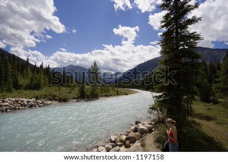 young woman at the bank of a river with glacial water - in the rockies, canada - stock photo