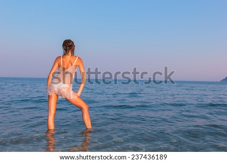 Young woman at the beach at dusk - stock photo
