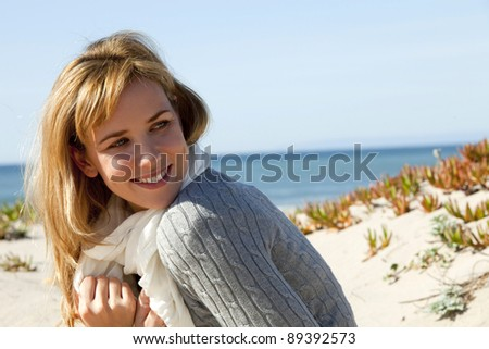 Young woman at the beach on a cold day - stock photo