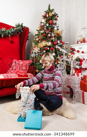 young woman at the Christmas tree unpacking presents and get clothes for newborns