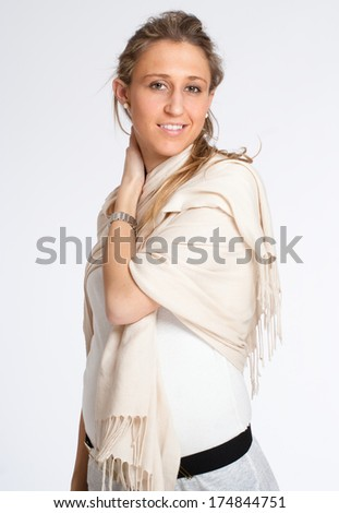 Young woman at the early stages of pregnancy, wearing a shawl - stock photo