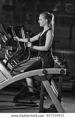 Young woman at the gym exercising. Run on on a machine. Jogging workout in dark fitness club. Cardio. Black and white. - stock photo