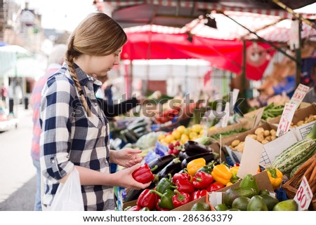 young woman at the market choosing her vegetables - stock photo