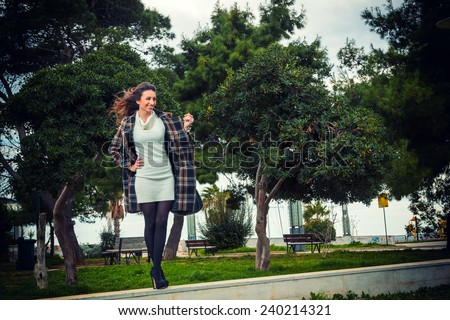 Young woman at the park on a windy day - stock photo