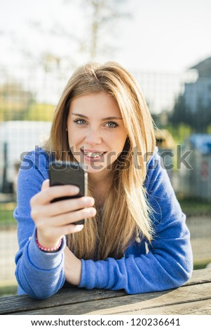 Young woman at the park with her smart phone - stock photo