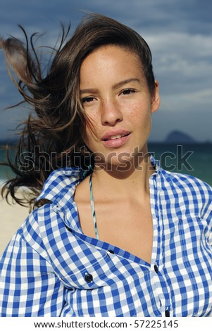 young woman at the sea blown over by the wind with tousled hair - stock photo
