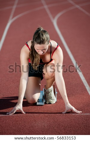 Young woman at the start of a running track - stock photo