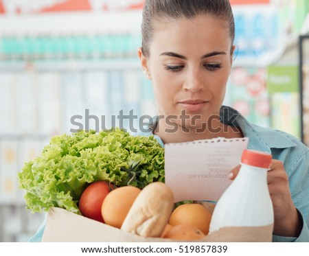 Young woman at the supermarket, she is checking a grocery list and holding a full shopping bag