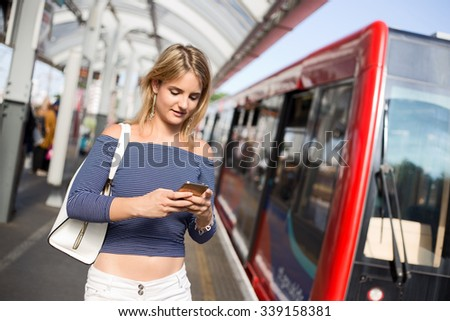 young woman at the train station using her phone - stock photo
