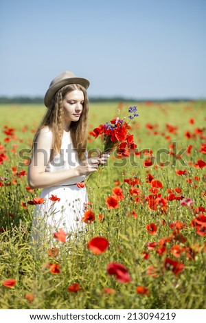 Young woman at white dress collects poppy bouquet - stock photo