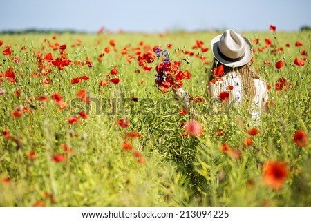 Young woman at white dress with poppy bouquet - stock photo