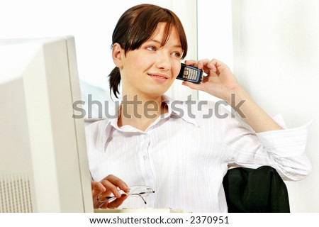 young woman at workplace in front of computer writing in agenda