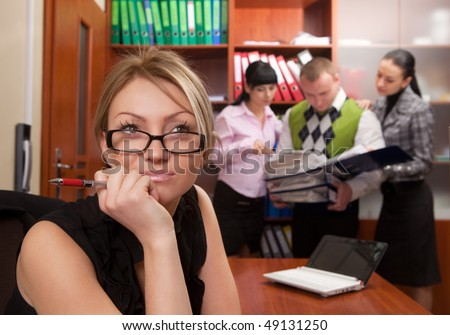 Young woman at workplace with coworkers on background - stock photo