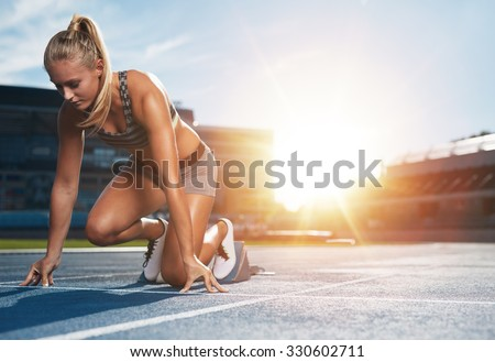 Young woman athlete at starting position ready to start a race. Female sprinter ready for sports exercise on racetrack with sun flare. - stock photo