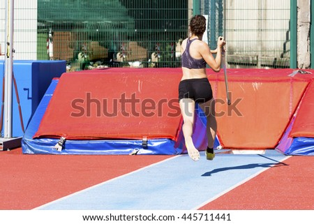 young woman athlete performs the high jump pole vault - stock photo