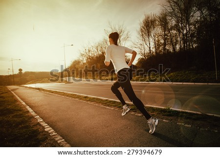 Young woman athlete running in nature at the sunrise  - stock photo