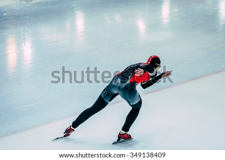 young woman athlete skater goes down track skating Palace. speed skating  indoors - stock photo