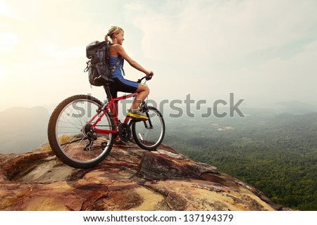Young woman athlete standing on top of a mountain with red bicycle and enjoying valley view - stock photo