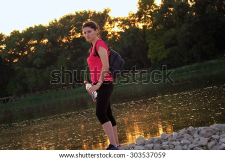 Young woman athlete with a bottle of water in her hand. Sunset behind with reflection in the lake. - stock photo