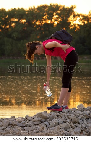 Young woman athlete with back pains during the workout. She is sitting near a lake in the evening with a bottle of water in the hand.  - stock photo