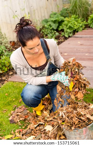 Young woman autumn gardening cleaning leaves in bucket