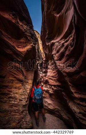 Young Woman Backpacker exploring narrow slot canyon Little Wild Horse Goblin Valley - stock photo