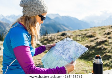 Young woman backpacker hiker reading map and camping in mountains on hiking trip, camping on sunset in Tatras, Poland. Drinking tea from thermos - stock photo