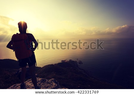 young woman backpacker hiking on seaside mountain peak