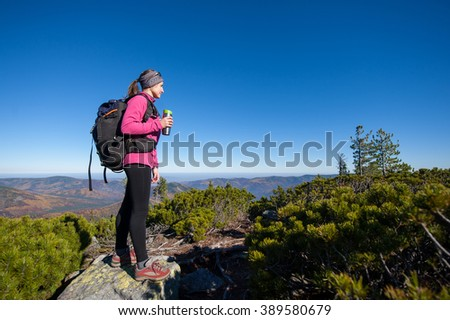 Young woman backpacker reaching her goal standing on peak of the mountain, holding cup of coffee and enjoying the beautiful landscape. Sunny autumn time. - stock photo