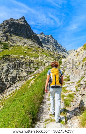 Young woman backpacker walking on hiking trail in summer landscape of High Tatra Mountains, Slovakia