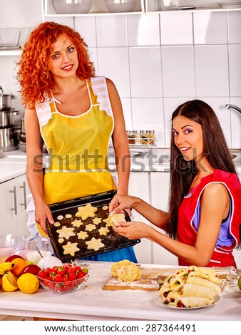 Young woman  baking cookies dough in oven.