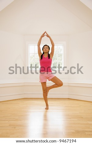 Young woman balancing in yoga tree pose. - stock photo