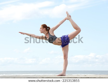Young woman balancing on one leg in yoga stretch position at the beach - stock photo