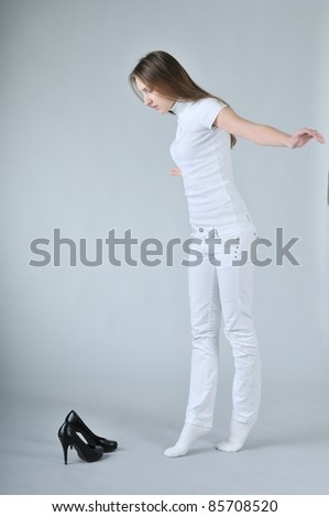 Young woman balancing on toes with high heels shoes placed on floor