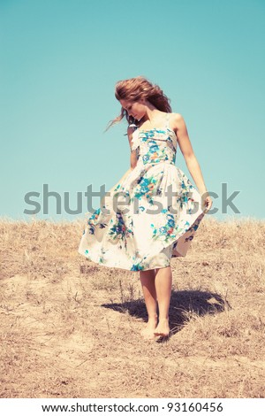 young woman barefoot in silk dress on top of the hill  sky in background, retro colours, grain added - stock photo