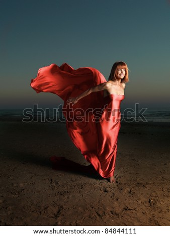 young woman beach red silk wind blowing