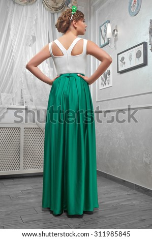 young woman, beautiful brunette in a long green dress, hands on hips; in the room,  back view. - stock photo