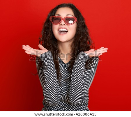 young woman beautiful portrait, posing on red background, long curly hair, sunglasses in heart shape, glamour concept - stock photo