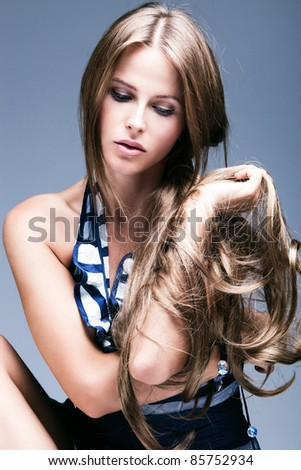young woman beauty portrait with long blond hair, studio shot, vertical - stock photo