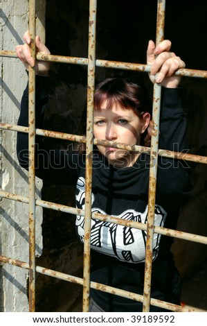 Young woman behind grate in a prison - stock photo