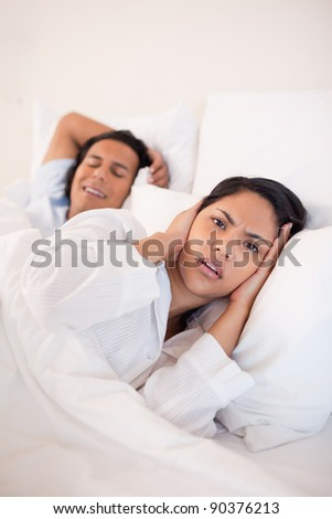 Young woman being annoyed by snoring boyfriend - stock photo