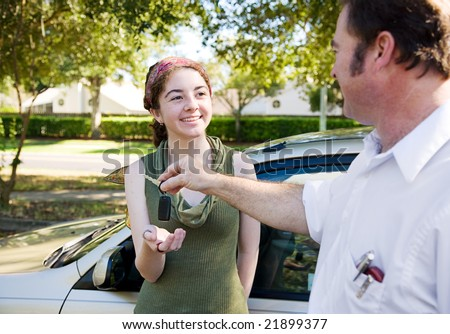 Young woman being handed the car keys by her father or driving instructor. - stock photo