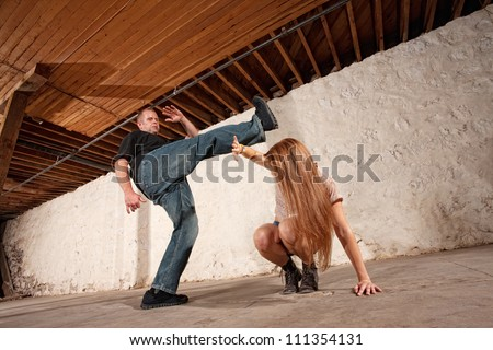 Young woman being kicked by Caucasian male - stock photo
