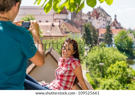 Young woman being photographed in romantic city on sunny day - stock photo